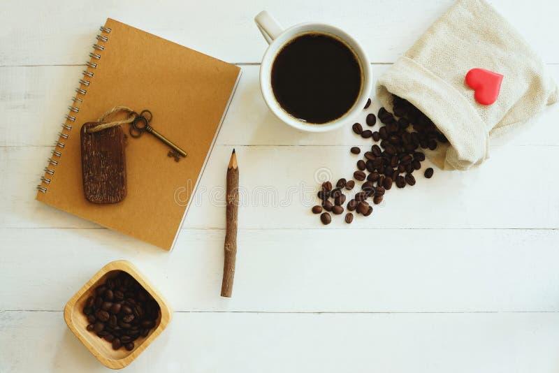 Witte kop van hete zwarte koffie, bruin notitieboekje, potlood, uitstekende die sleutel, koffieboon op witte lijstachtergrond wor royalty-vrije stock afbeelding
