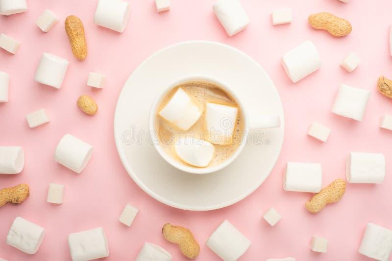 Witte kop van koffie met heemst, en heemst, en kubussen van suiker, en noten rond op een roze achtergrond Mogelijkheid aan royalty-vrije stock foto