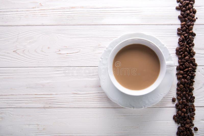 Witte kop van koffie met melk of thee met melk op witte houten die achtergrond met koffiebonen wordt verfraaid stock foto