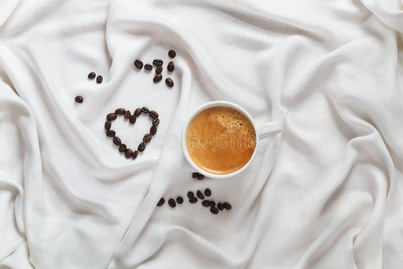 Witte kop van koffie op een zijdestof Verspreide koffiebonen in de vorm van een hart Romantisch ontbijt voor de Dag van Valentine royalty-vrije stock fotografie