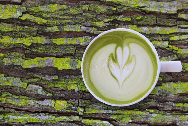 Witte kop van kunst van de matcha de groene thee latte met schuim op rustiek mos houten lijst met exemplaarruimte stock fotografie
