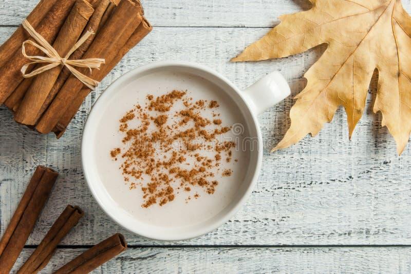 Witte kop van salep melkachtige hete drank van Turkije met kaneelpoeder en stokken gezond kruid en het blad van de de herfstwinte stock foto