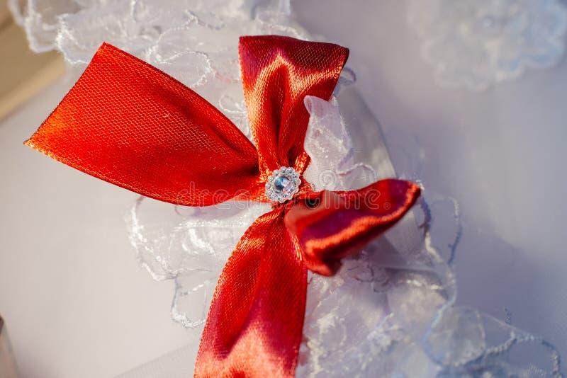 Witte kouseband van de bruid met een rode boog stock fotografie