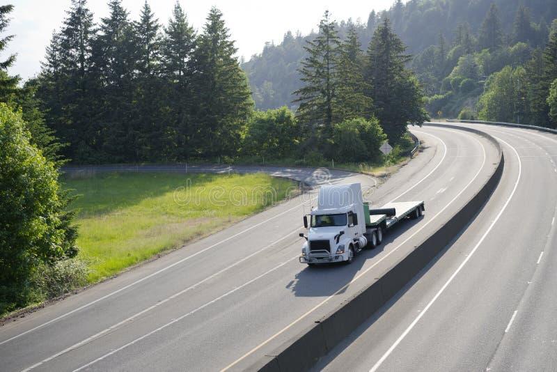 Witte krachtige grote installatie semi vrachtwagen met stap - onderaan semi aanhangwagendr. royalty-vrije stock foto