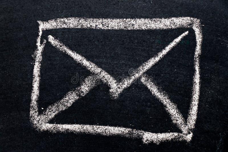 Witte krijttekening in het pictogram van de postenvelop op zwarte raad stock foto's