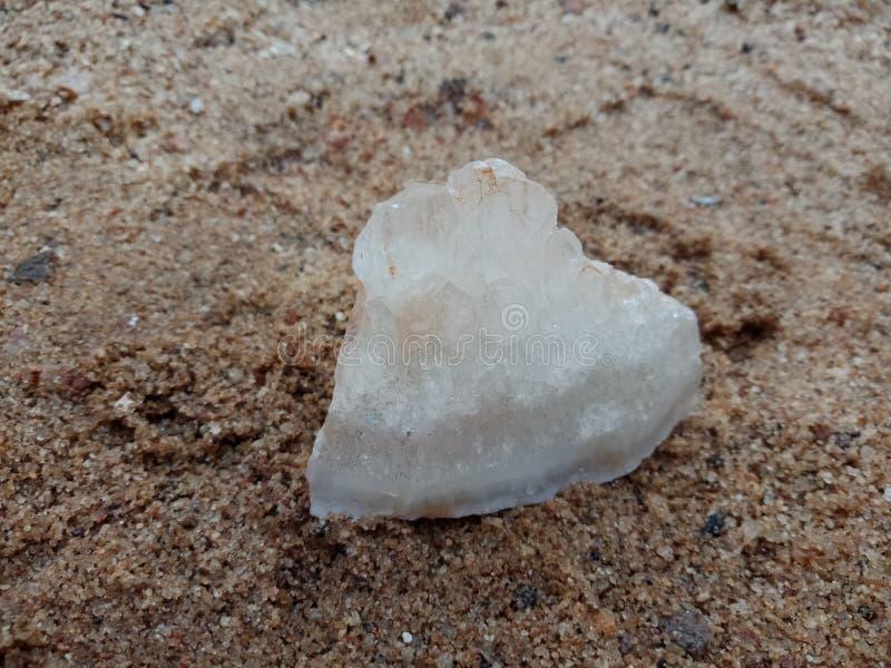 Witte kristalsteen met textuur op het zand geweven behang als achtergrond, strand Oceaan royalty-vrije stock fotografie