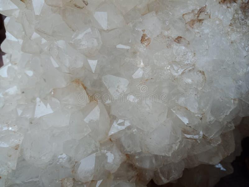 Witte kristalsteen op het zand met textuur geweven behang als achtergrond, strand Oceaan royalty-vrije stock afbeeldingen