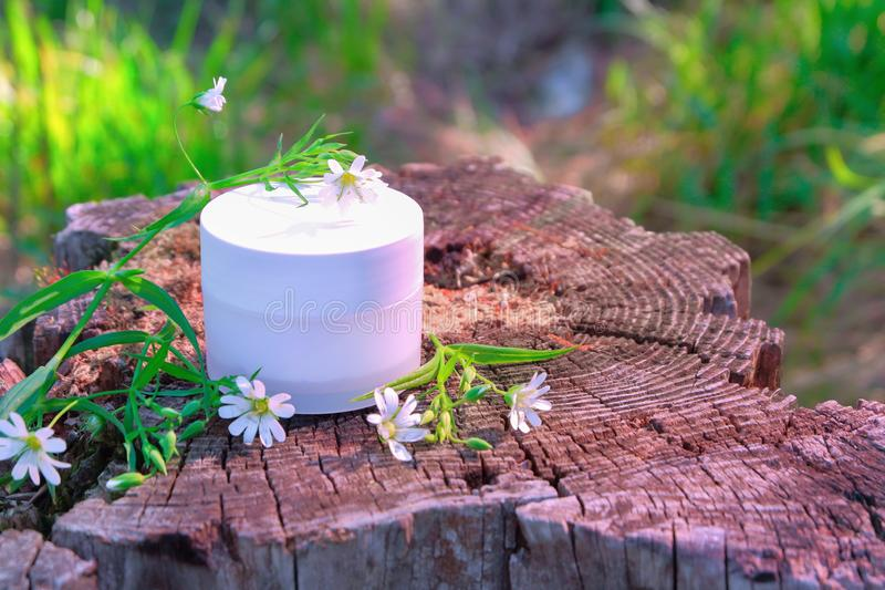 Witte kruik met kosmetische room op een houten stomp met wildflowers en groen gras op een heldere de zomer Zonnige dag royalty-vrije stock afbeeldingen