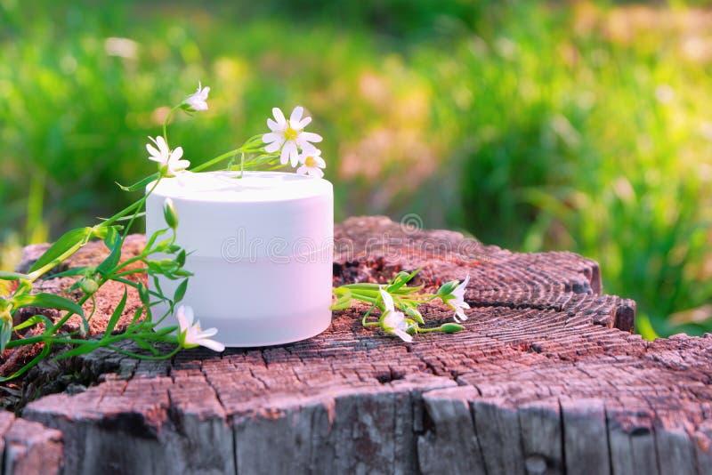 Witte kruik met kosmetische room in openlucht met wilde bloemen en groen gras royalty-vrije stock afbeelding