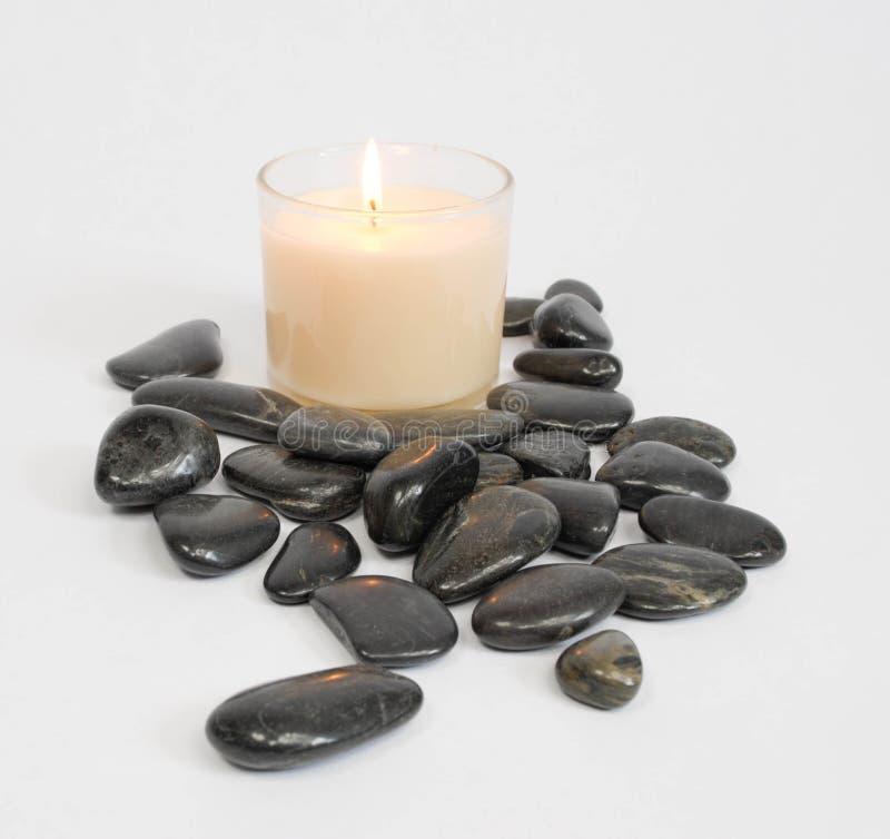 Witte kaars met zwarte stenen royalty-vrije stock afbeelding