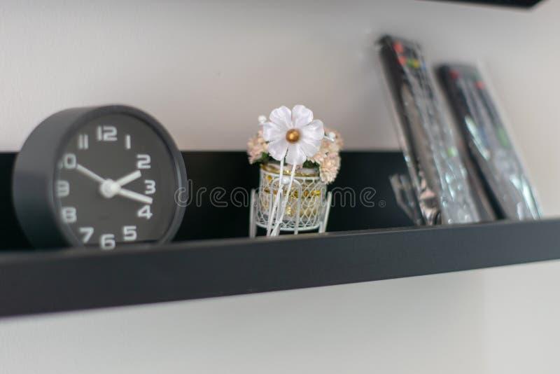 Witte kunstbloemen naast de zwarte wekker royalty-vrije stock afbeelding