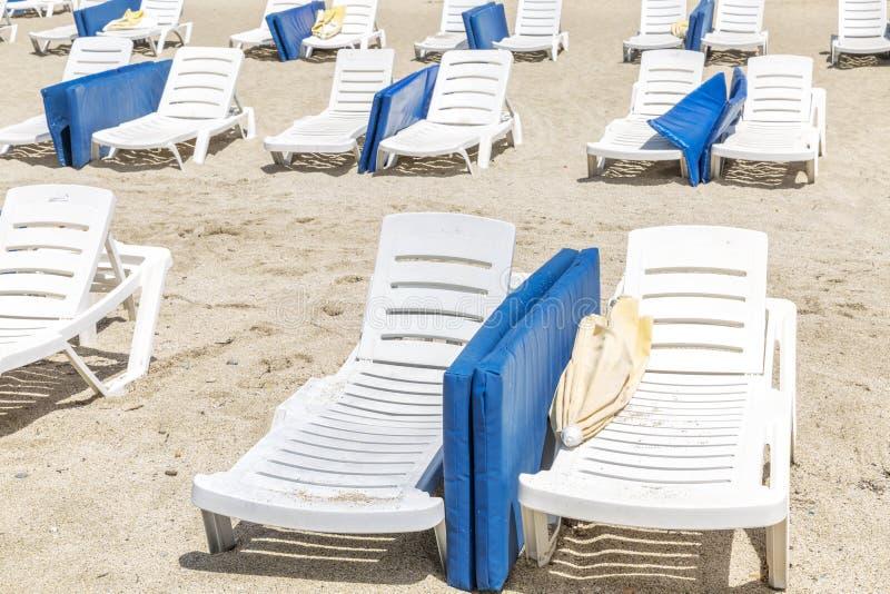Witte lanterfanters met blauwe matrassen op een openbaar strand stock foto