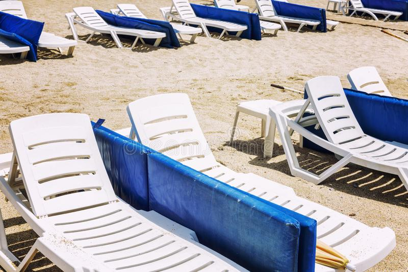 Witte lanterfanters met blauwe matrassen op een openbaar zandig strand royalty-vrije stock afbeelding