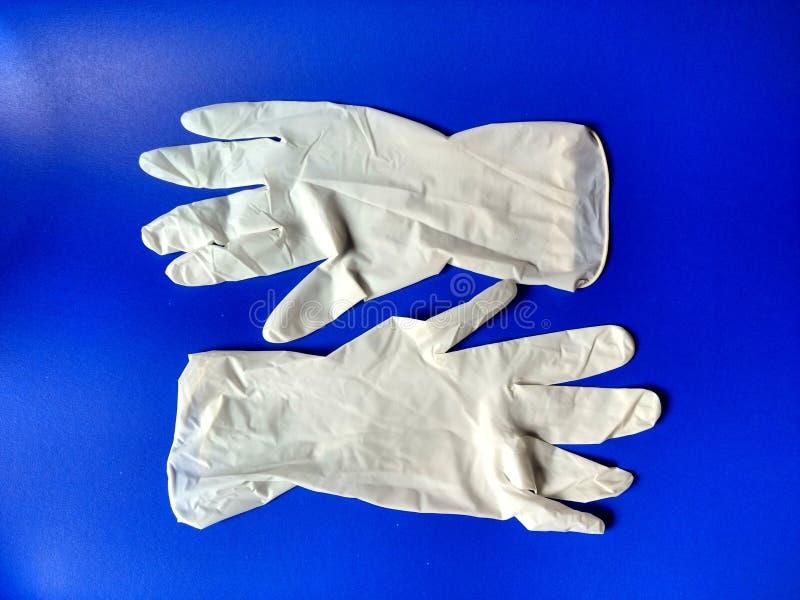 Witte latexhandschoenen met blauwe achtergrond royalty-vrije stock foto's