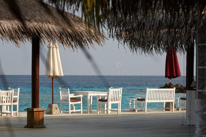 Witte lege lijstlijst en stoelen bij tropische resrraunt op open terras in de Maldiven Blauwe oceaanlagune op achtergrond royalty-vrije stock afbeeldingen
