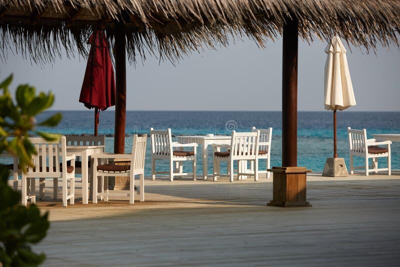 Witte lege lijstlijst en stoelen bij tropische resrraunt op open terras in de Maldiven Blauwe oceaanlagune op achtergrond stock foto's
