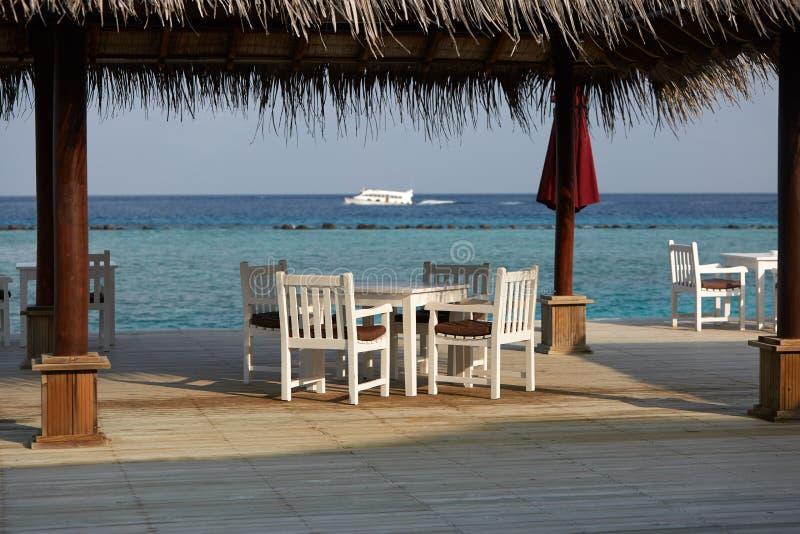 Witte lege lijstlijst en stoelen bij tropische resrraunt op open terras in de Maldiven Blauwe oceaanlagune op achtergrond royalty-vrije stock foto