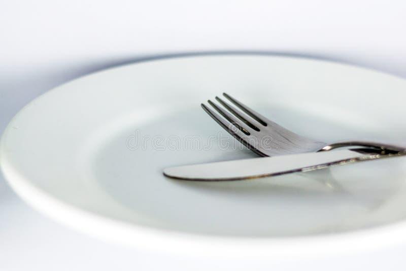Witte lege plaat met vork en mes stock afbeelding
