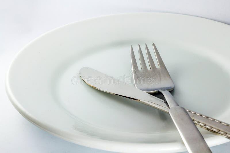 Witte lege plaat met vork en mes stock afbeeldingen