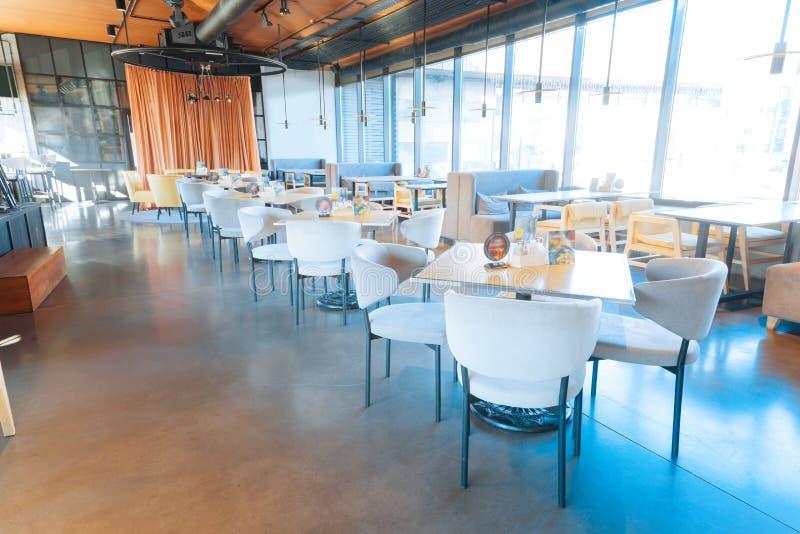 Witte leunstoelen die op z'n gemak zich dichtbij houten lijsten in restaurant bevinden royalty-vrije stock afbeeldingen