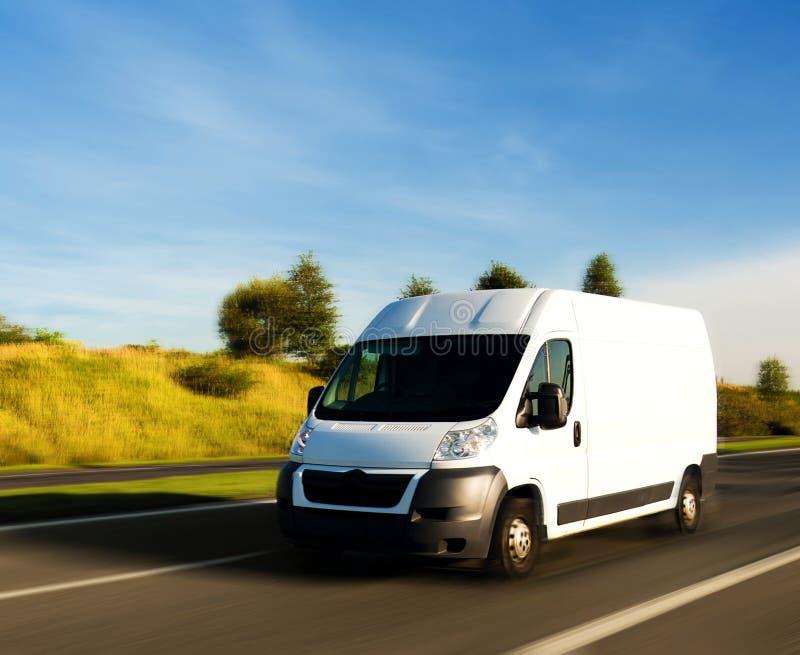 Witte leveringsbestelwagen op weg stock afbeeldingen