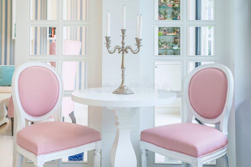 Witte lijst en roze stoel met kaars op lijst in woonkamer Stoel woonkamer