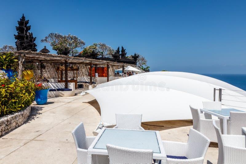 Witte lijsten en stoelen bij een openluchtklippenkoffie met oceaanmening stock foto's