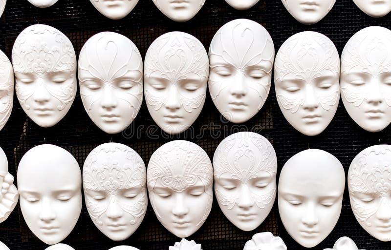 Witte maskers op een zwarte achtergrond stock afbeeldingen