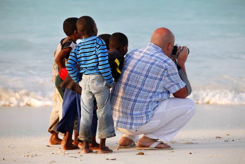 Witte mens met Afrikaanse kinderen stock foto's