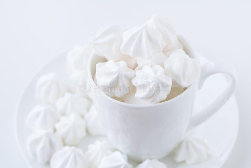 Witte merengue in de witte theekop op witte achtergrond stock foto's