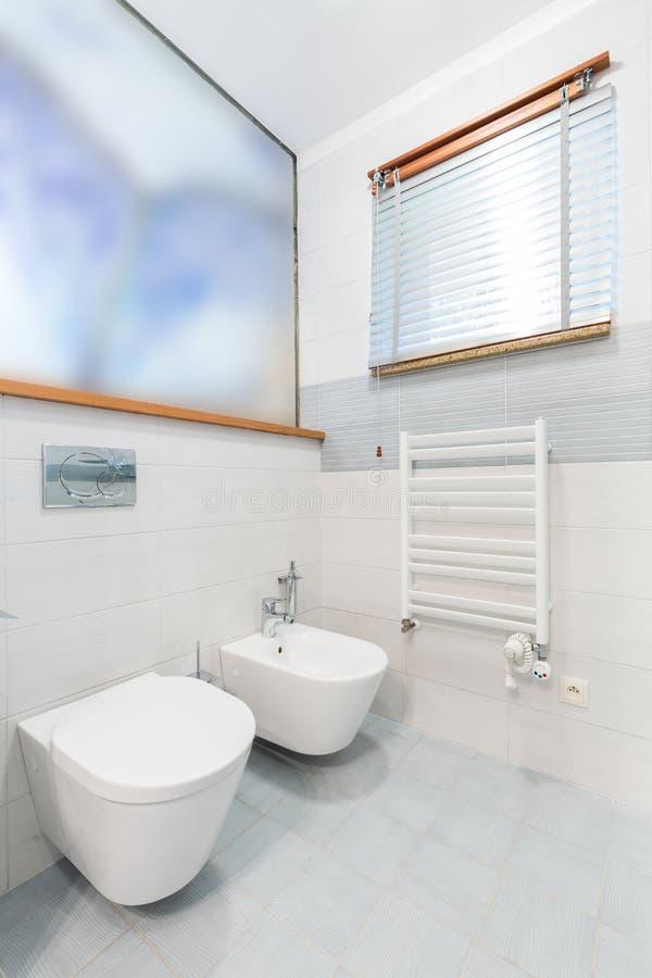 Witte minimalistische badkamers met toilet en bidet stock foto's