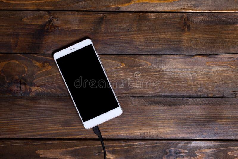Witte mobiele telefoon houten achtergrond houten het laden kabel stock foto's
