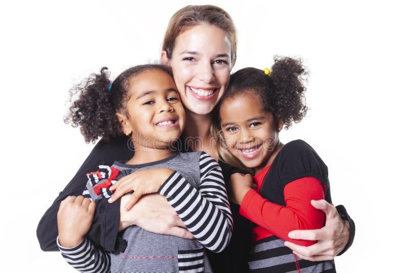 Witte moeder met het zwarte kindfamilie stellen op een witte studio als achtergrond royalty-vrije stock afbeeldingen