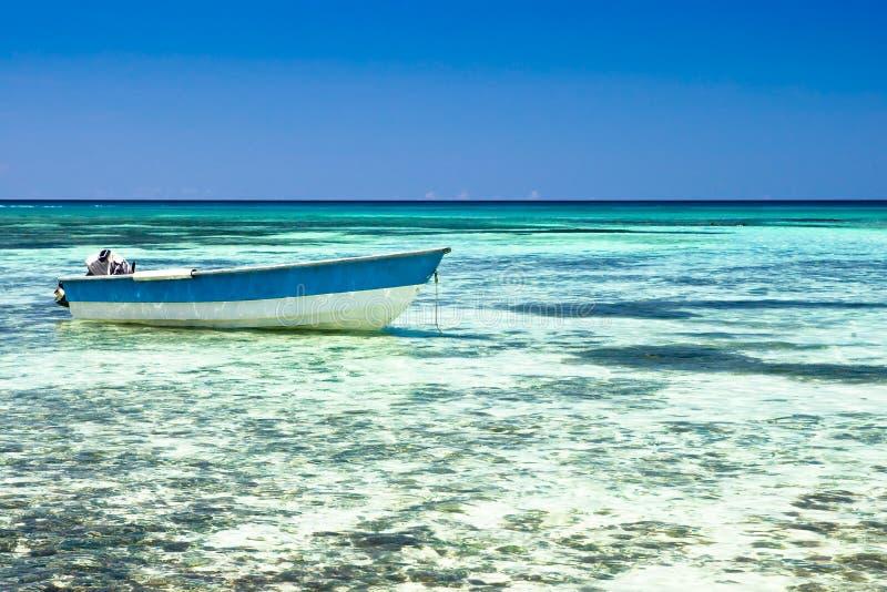 Witte motorboot op een zandstrand in de oceaan stock foto's