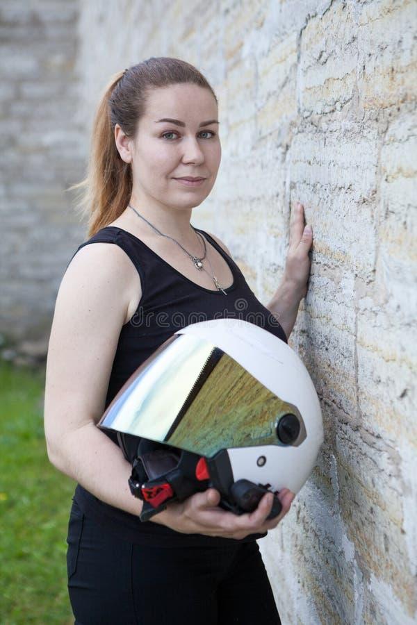 Witte open gezichtshelm met spiegelschild in handen van mooie vrouwenmotorrijder, portret dichtbij steenmuur stock foto