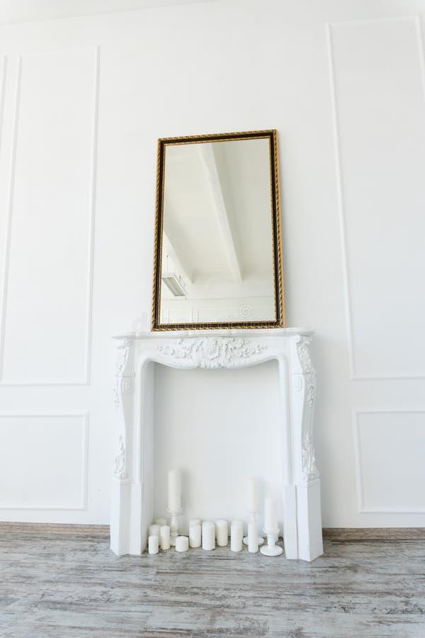 Witte open haard met een spiegel boven het in een lege ruimte stock afbeelding