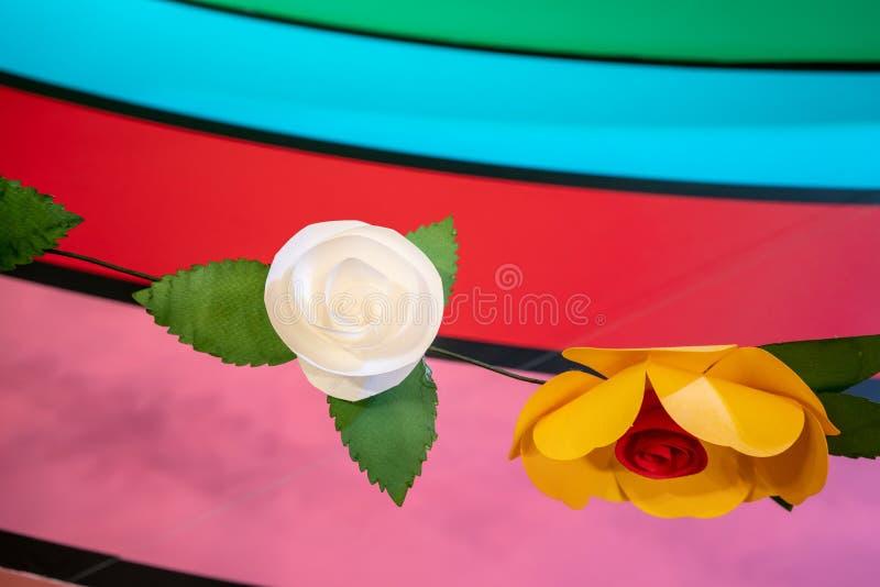 Witte, oranje en rode document bloemen tegen regenboogachtergrond stock afbeeldingen