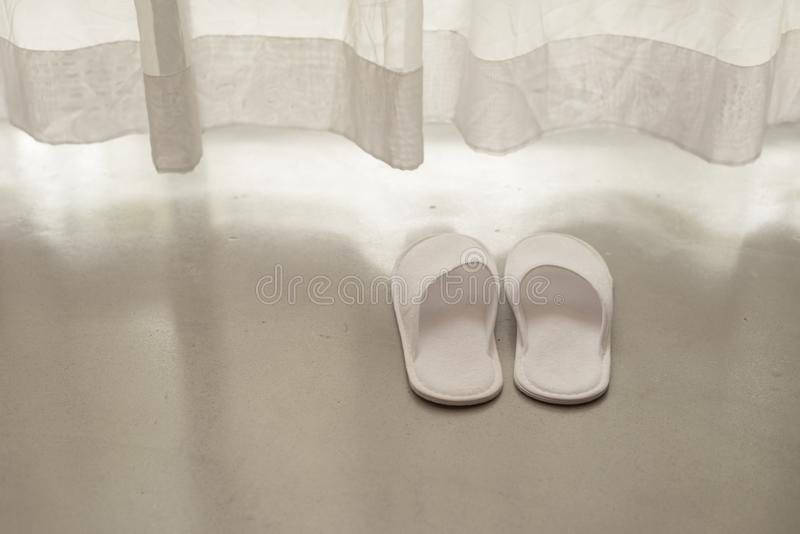 Witte pantoffels door witte zuivere gordijnen en zacht zonlicht royalty-vrije stock foto