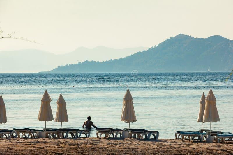 Witte paraplu's, blauwe overzees en grote bergen op horizon stock foto's