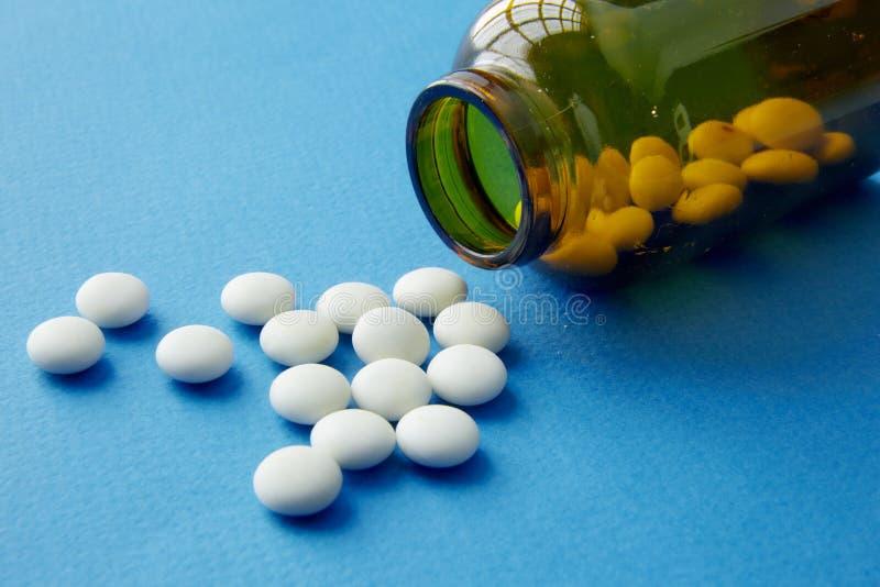 Witte pillen uit een bruine flessengeneeskunde stock foto's