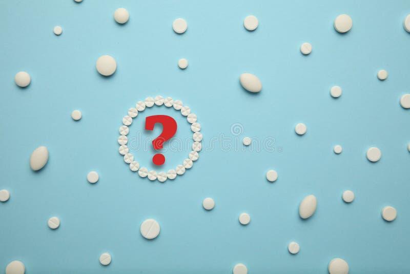 Witte pillen voor pijnhulp en behandeling op een blauwe achtergrond Vraagteken, de keus van drugs stock afbeeldingen