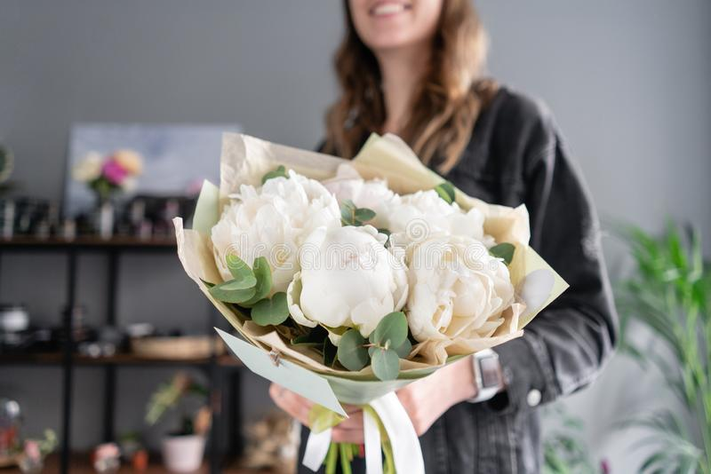 Witte pioenen in de handen van de vrouw Mooie verse pioenbloem voor catalogus of online opslag Bloemenwinkelconcept Bloemen royalty-vrije stock fotografie