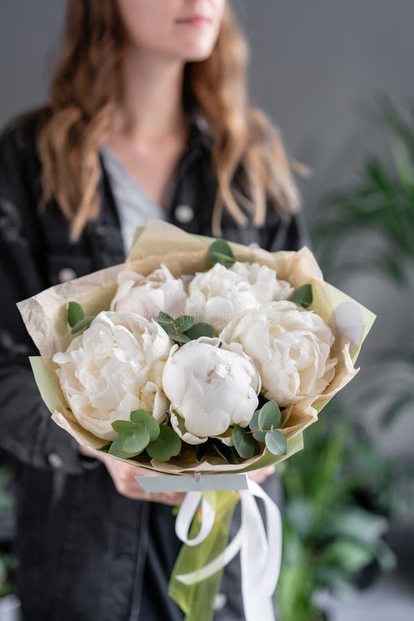 Witte pioenen in de handen van de vrouw Mooie verse pioenbloem voor catalogus of online opslag Bloemenwinkelconcept Bloemen stock fotografie