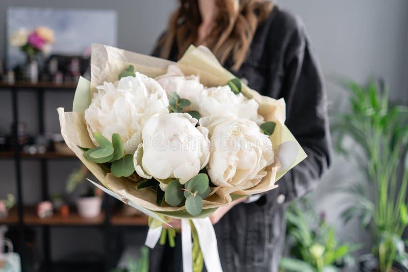 Witte pioenen in de handen van de vrouw Mooie verse pioenbloem voor catalogus of online opslag Bloemenwinkelconcept Bloemen stock foto
