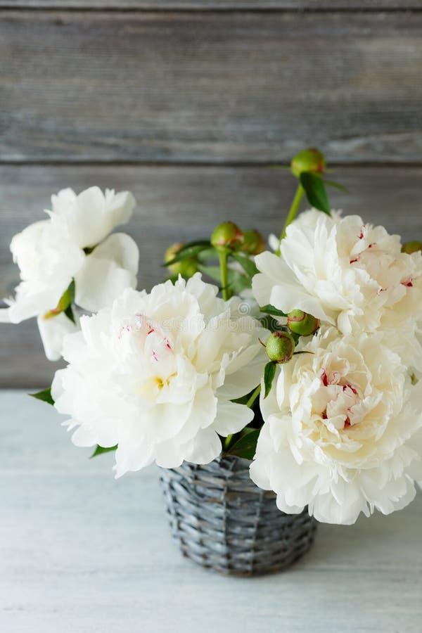 Witte pioenen in een rieten vaas royalty-vrije stock foto's