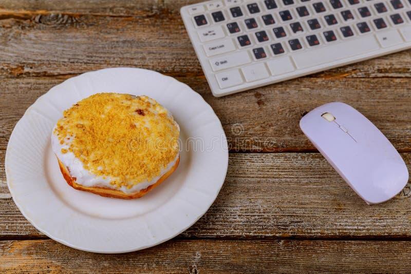Witte plaat met doughnut en laptop toetsenbord op houten lijst stock foto's