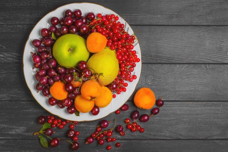 Witte plaat met een assortiment van verse tuinvruchten en berrie stock afbeeldingen