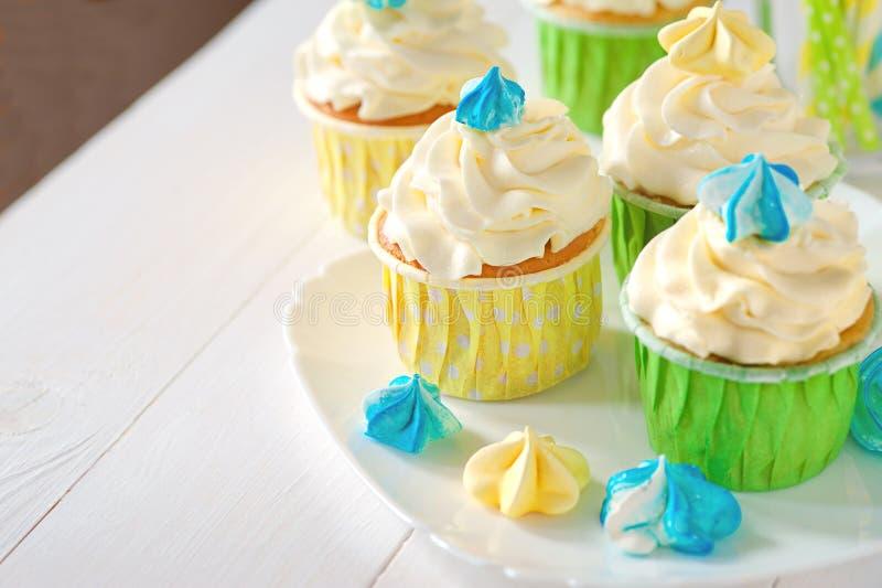 Witte plaat met mooie cupcakes op houten achtergrond, close-up Plaats voor inschrijving royalty-vrije stock foto