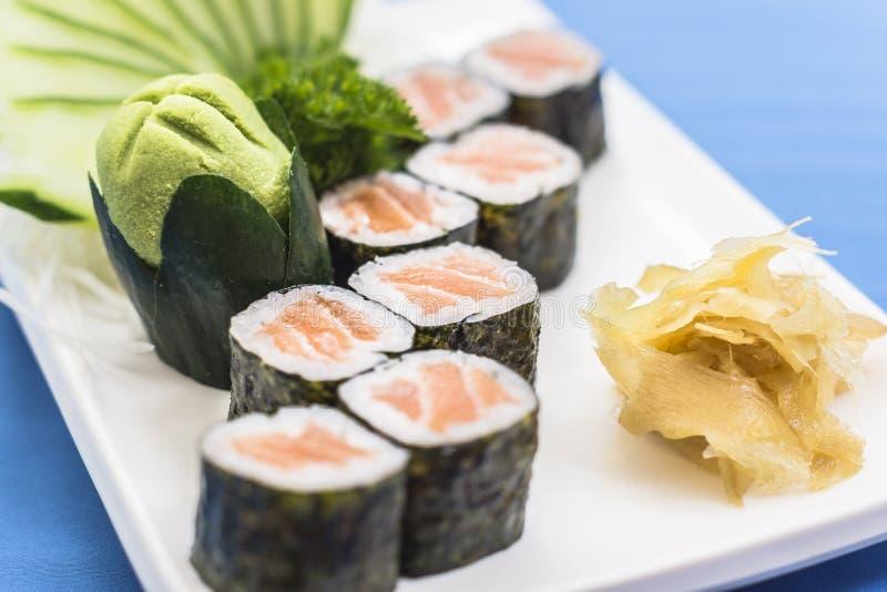 Witte plaat met salmaosushis, wasabi en gember stock afbeelding