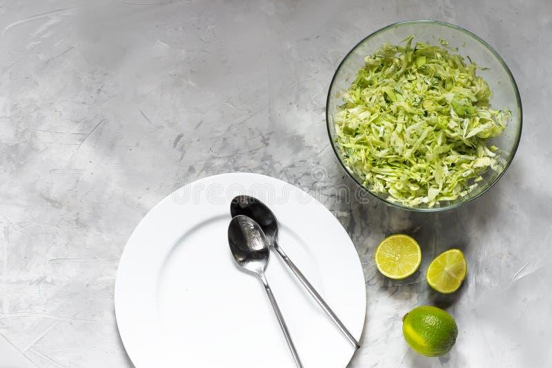Witte plaat met soeplepels en salade van verse kool met greens stock afbeeldingen